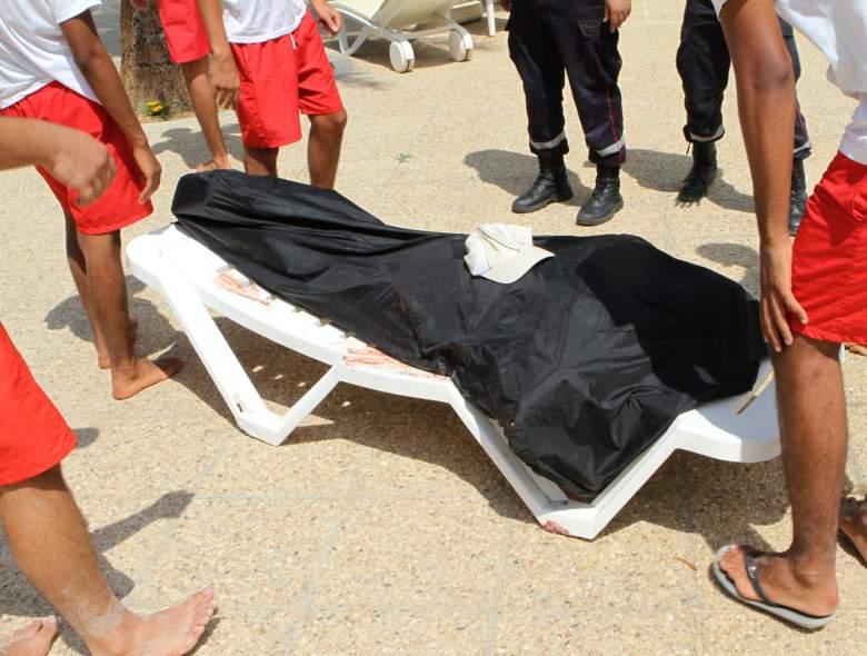 Salvavidas rodean el cuerpo sin vida bajo una manta negra en la playa en Túnez.  (Foto deBECHIR TAIEB/AFP/Getty Images)