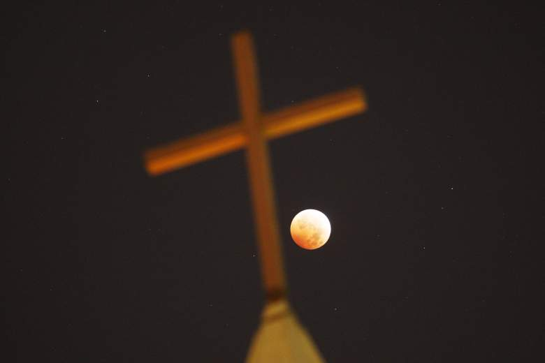 Una cruz religiosa iluminada durante un eclipse total en octubre de 2014. Algunos, como John Hagee, dicen que la cuarta luna de sangre es una profecía para el desastre y los tiempos finales.