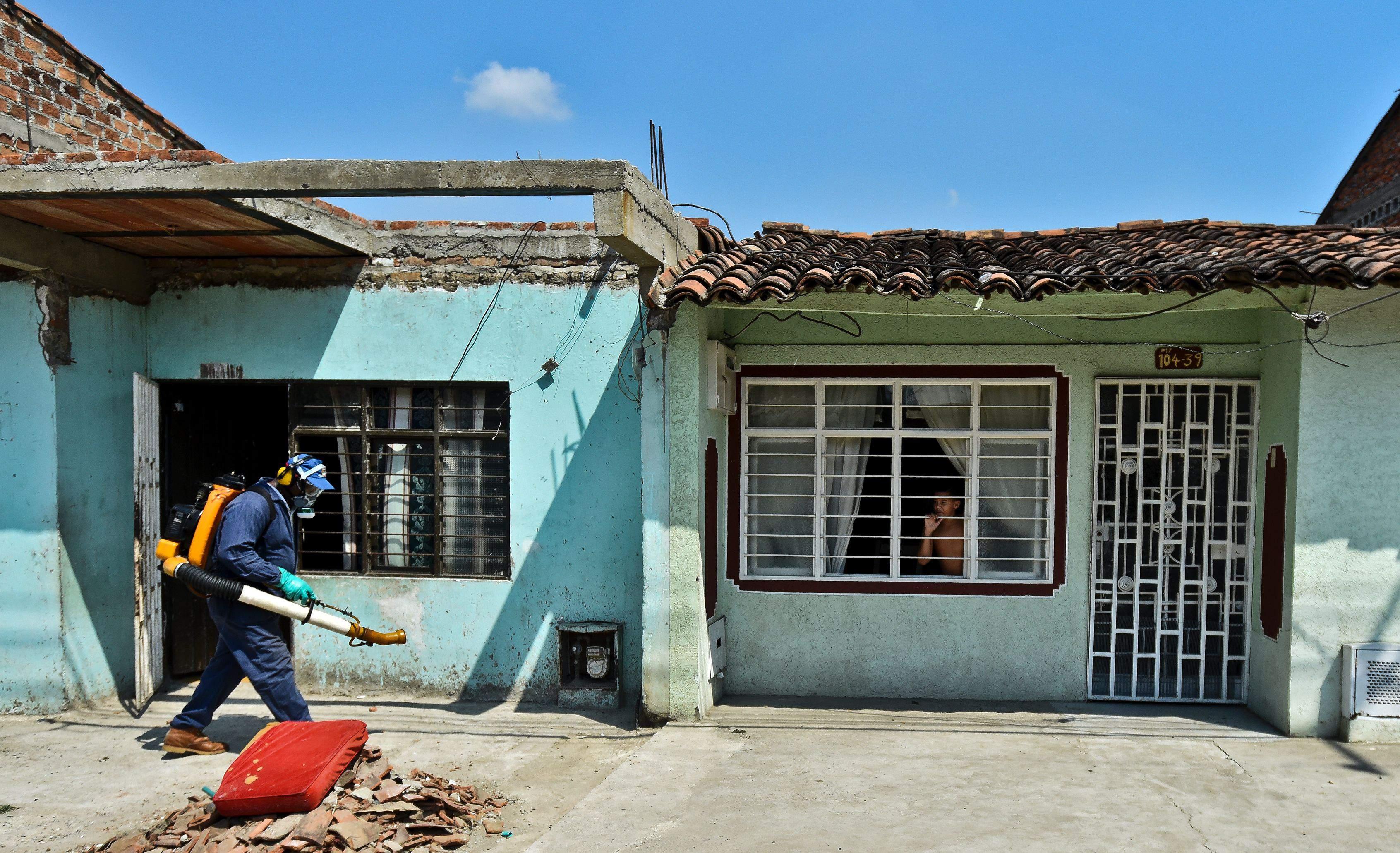 Un empleado de la Secretaría de Salud fumiga contra el mosquito Aedes Aegypti fuera de las casas de Cali, Colombia. (Getty)