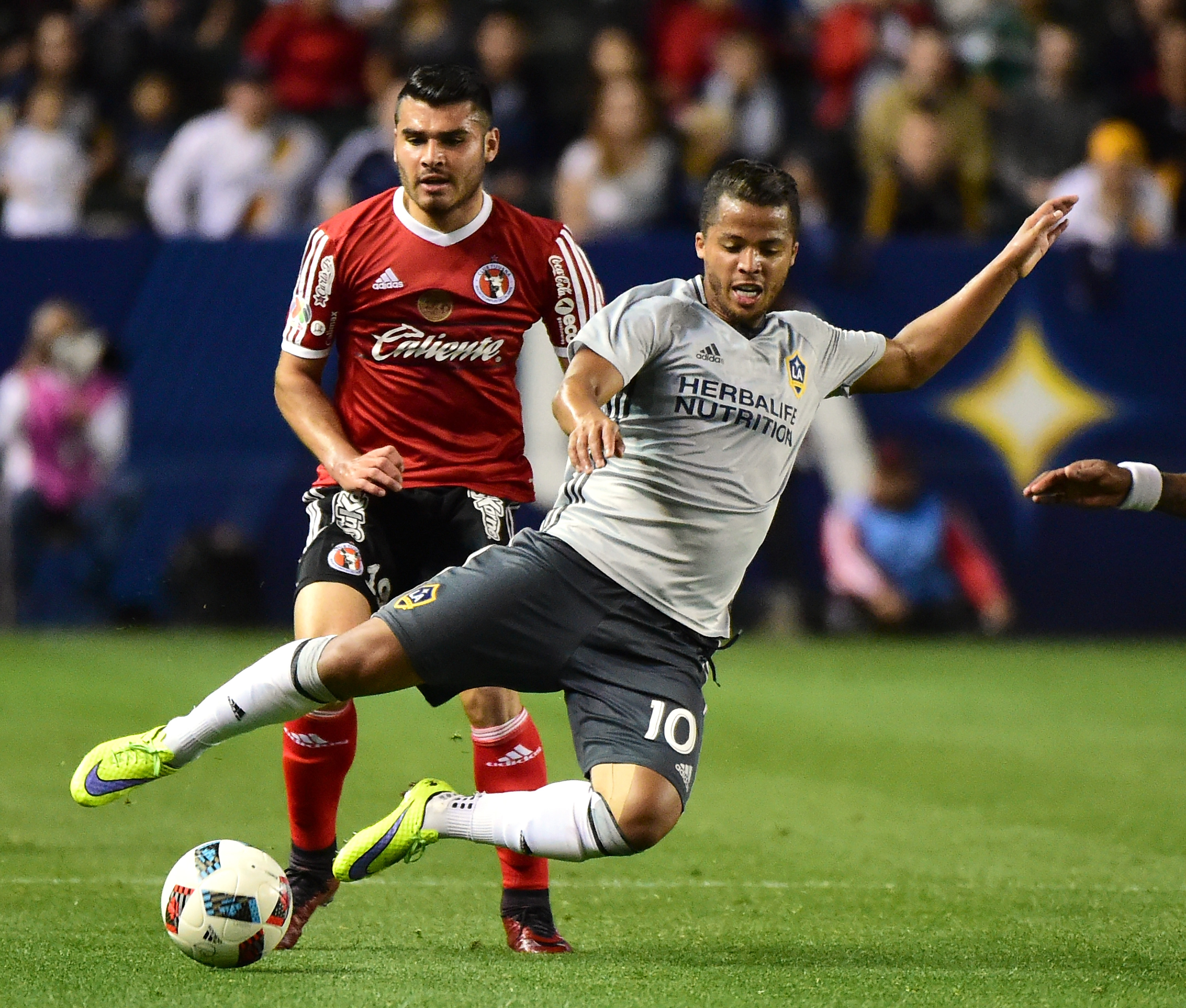 CARSON, CA - FEBRUARY 09: Giovani Dos Santos #10 of Los Angeles Galaxy is tripped by Alberto Garcia #19 of Club Tijuana during the second half at StubHub Center on February 9, 2016 in Carson, California. (Photo by Harry How/Getty Images)
