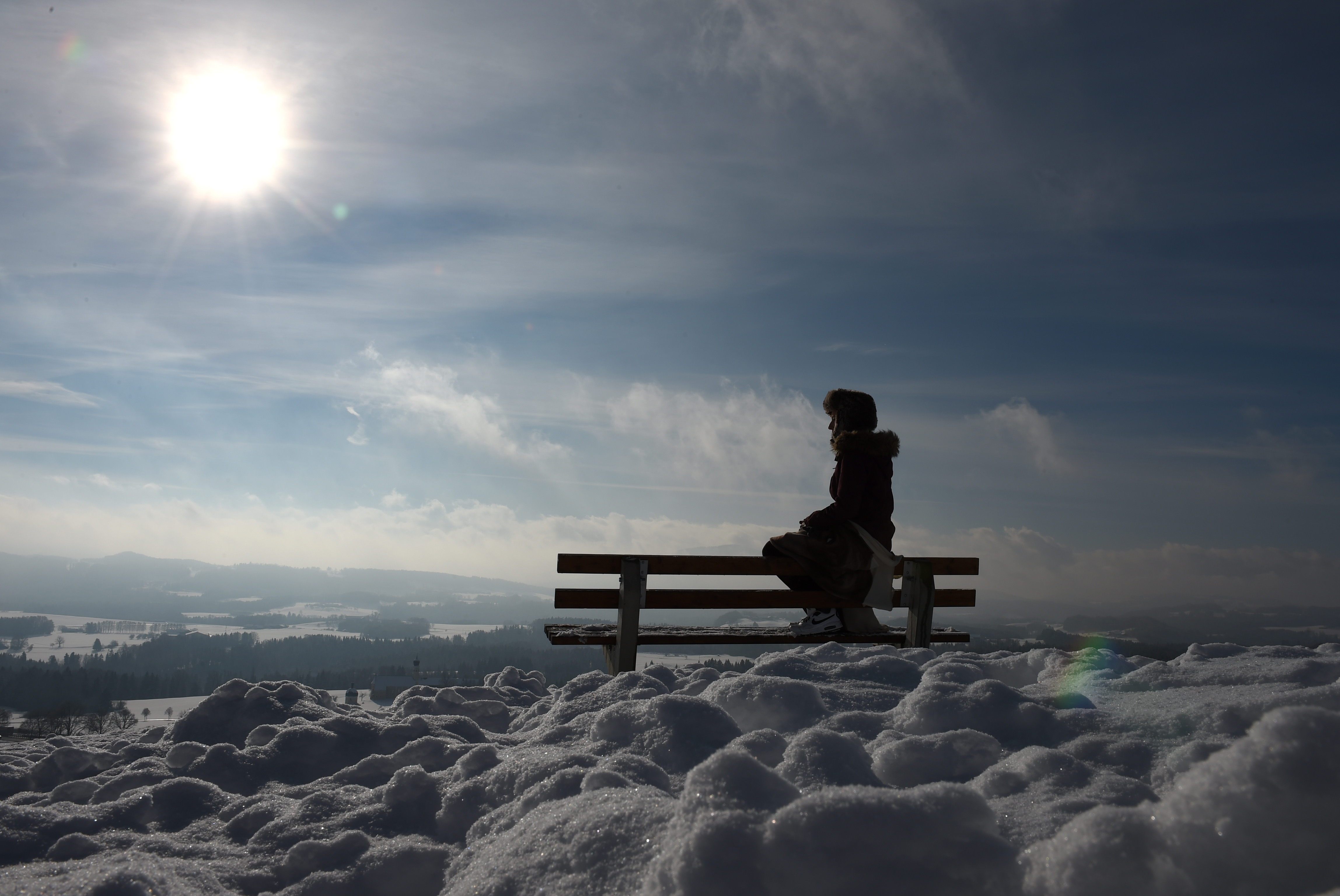 Navidad 2017: Versículos y Oraciones de la Biblia para compartir - A young girl sits on a bench and enjoys the sunny winter weather with temperatures by the freezing point at a snowy landscape near the small Bavarian village Irschenberg, southern Germany, on January 20, 2016. / AFP / Christof STACHE (Photo credit should read CHRISTOF STACHE/AFP/Getty Images)