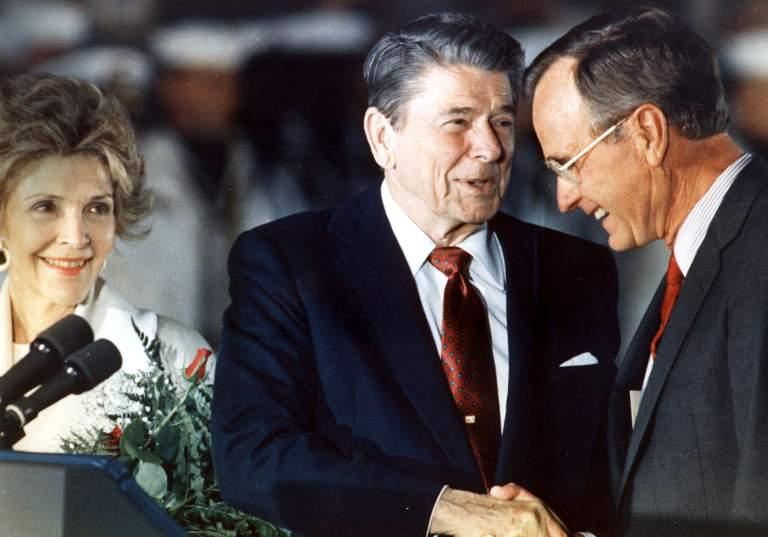 El presidente Ronald Reagan y el vicepresidente George Bush se dan la mano como primera dama Nancy Reagan mira en estado de 1991. (Getty)