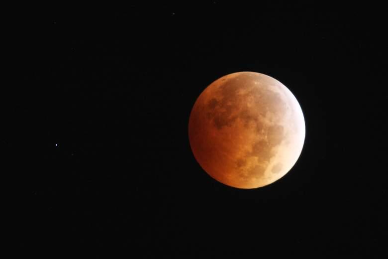 """La luna es iluminada por la luz solar reflejada en la Tierra durante un eclipse lunar total, una de las cuatro llamadas """"lunas de sangre"""", el 8 de octubre de 2014 en Los Ángeles, California."""