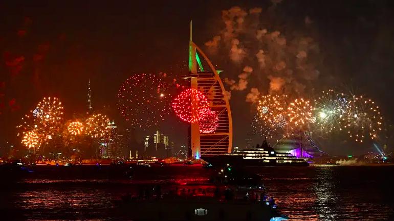 Las celebraciones de fuegos artificiales de Año Nuevo se ven sobre el horizonte de Dubai con el Burj Al Arab (R) y el Burj Khalifa (L), el edificio más alto del mundo, el 31 de diciembre de 2019.