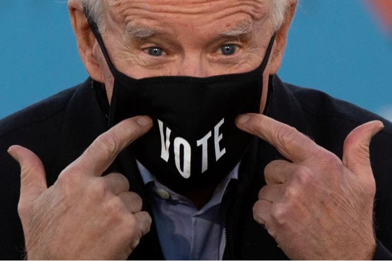 """El presidente electo Joe Biden señala su máscara facial con la palabra """"Vote"""" impresa en ella."""