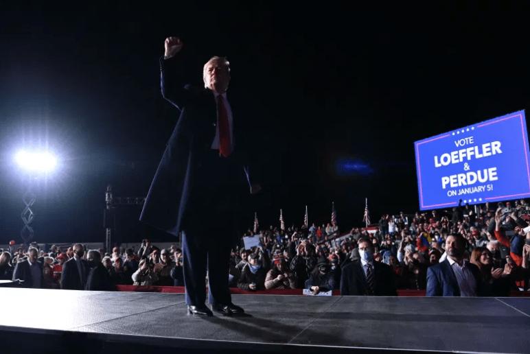 Trump levanta el puño después de hablar durante un mitin.