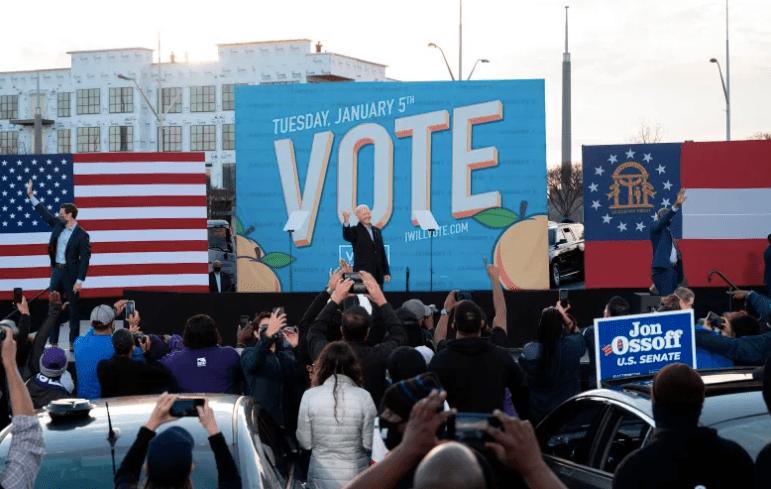 Los candidatos demócratas al Senado Jon Ossoff (L), Raphael Warnock (R) y el Presidente electo Joe Biden (C) saludan desde el escenario.