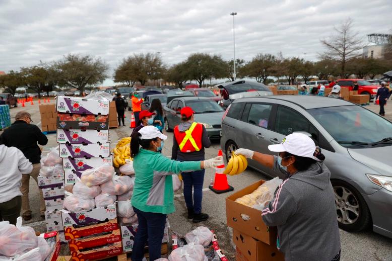 Los voluntarios se preparan para cargar alimentos en los automóviles durante la distribución de alimentos del Houston Food Bank en el NRG Stadium el 21 de febrero de 2021 en Houston, Texas. Miles de personas hicieron fila para recibir alimentos y agua en un sitio de distribución masiva para los residentes de Houston que aún no tienen agua corriente ni electricidad después de la tormenta invernal Uri.