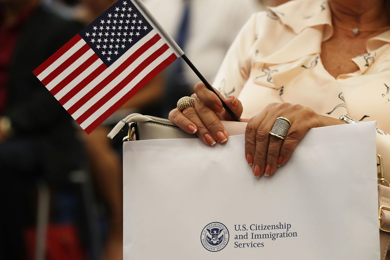 Una persona sostiene una bandera estadounidense mientras participan en la ceremonia para convertirse en ciudadano  durante la naturalización del Servicio de Inmigración en la Oficina de Campo de Miami el 17 de agosto de 2018 en Miami, Florida.
