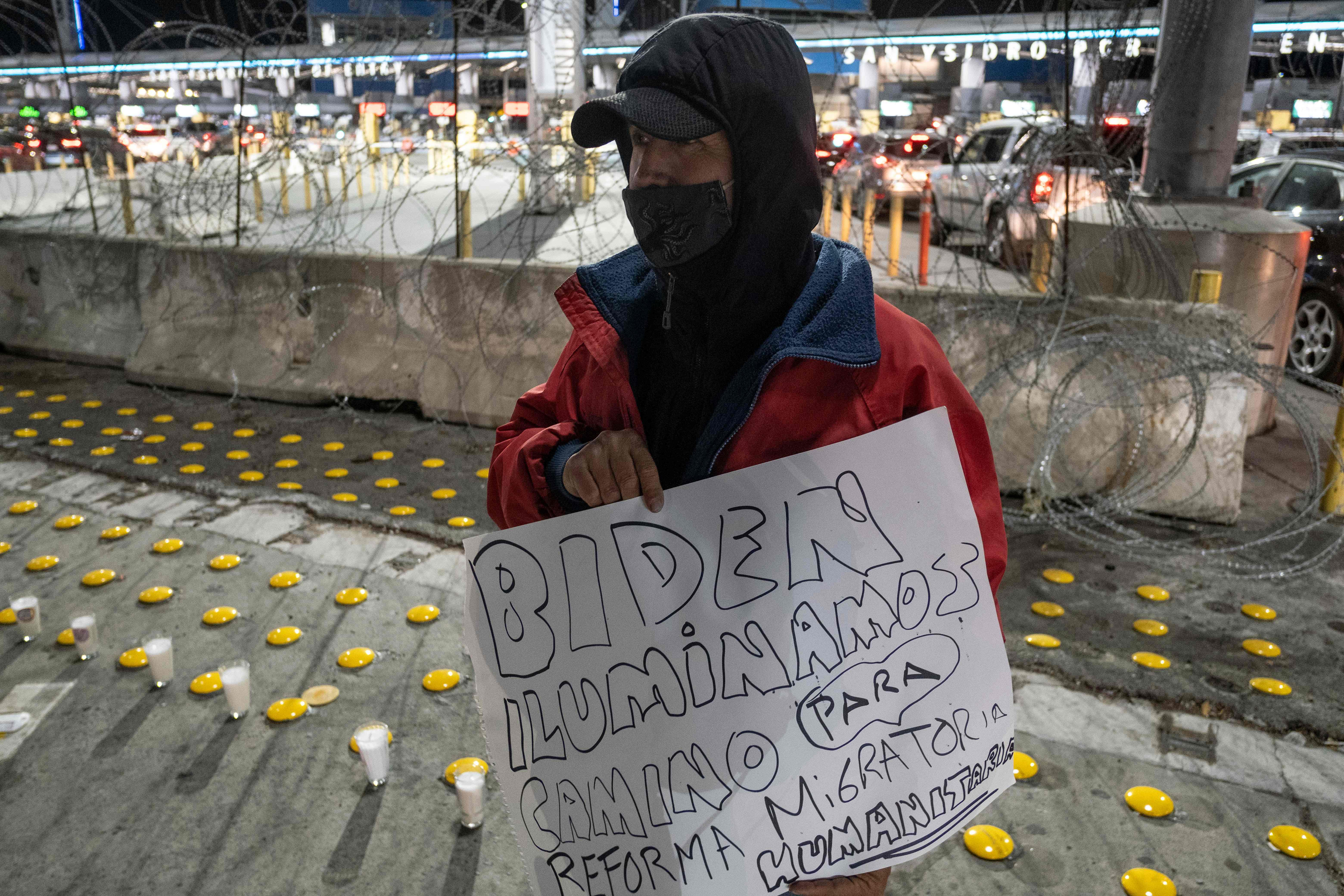 """Un migrante sostiene un cartel que dice """"Biden: ilumine el camino para una reforma migratoria humana"""", como se manifiestan defensores y migrantes en el puerto de cruce de San Ysidro durante una vigilia llamada """"Camino hacia una reforma migratoria humana"""", en Tijuana, estado de Baja California, México el 19 de enero de 2021,"""