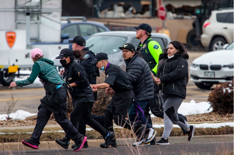 Los compradores son evacuados de una tienda de comestibles King Soopers después de que un hombre armado abrió fuego el 22 de marzo de 2021 en Boulder, Colorado.