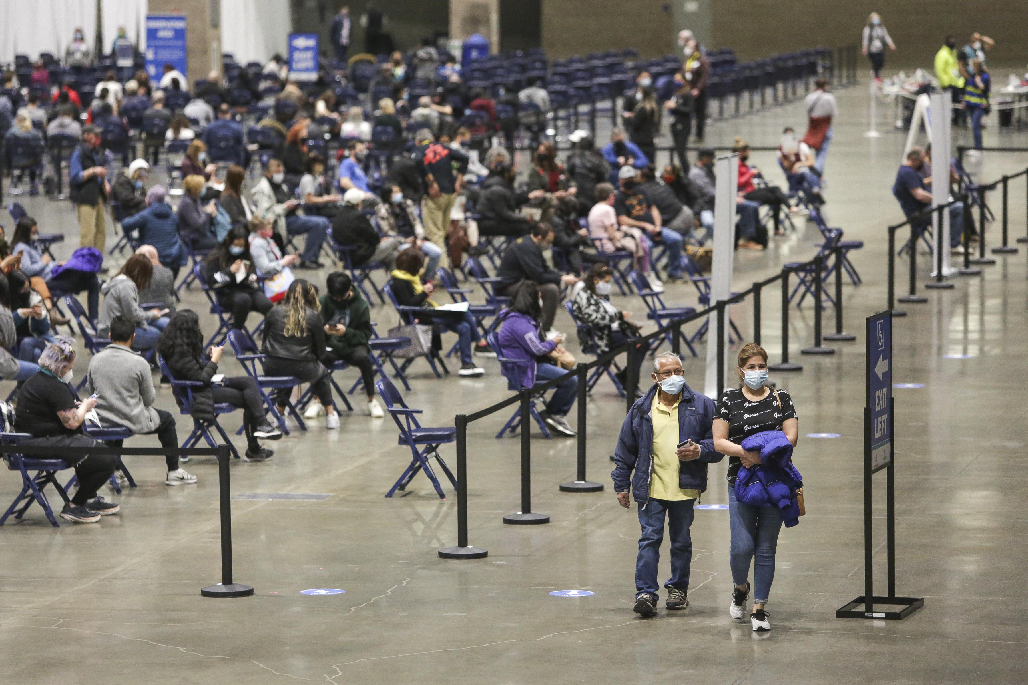 Las personas parten después de recibir la vacuna Pfizer Covid-19 durante el día de apertura del sitio de vacunación comunitaria, una colaboración entre la ciudad de Seattle, First & amp; Goal Inc. y Swedish Health Services en el Lumen Field Event Center en Seattle, Washington, el 13 de marzo de 2021.