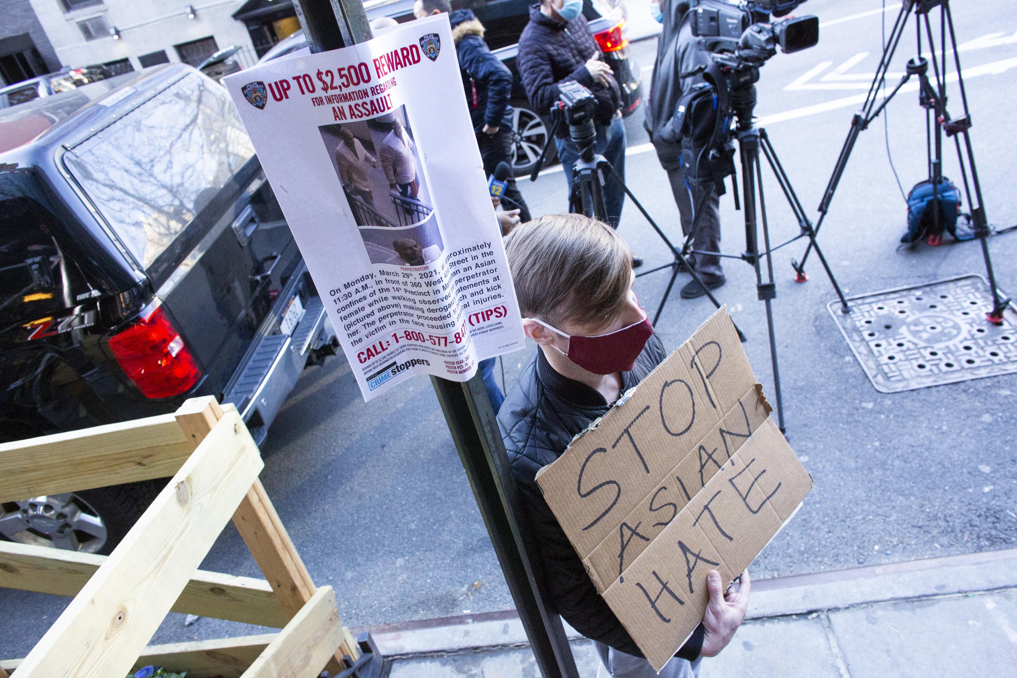 Un cartel de un sospechoso cuelga de un poste mientras un hombre sostiene un cartel después de una conferencia de prensa antiviolencia estadounidense de origen asiático el 30 de marzo de 2021, afuera del edificio donde una mujer asiática de 65 años fue atacada en Nueva York.
