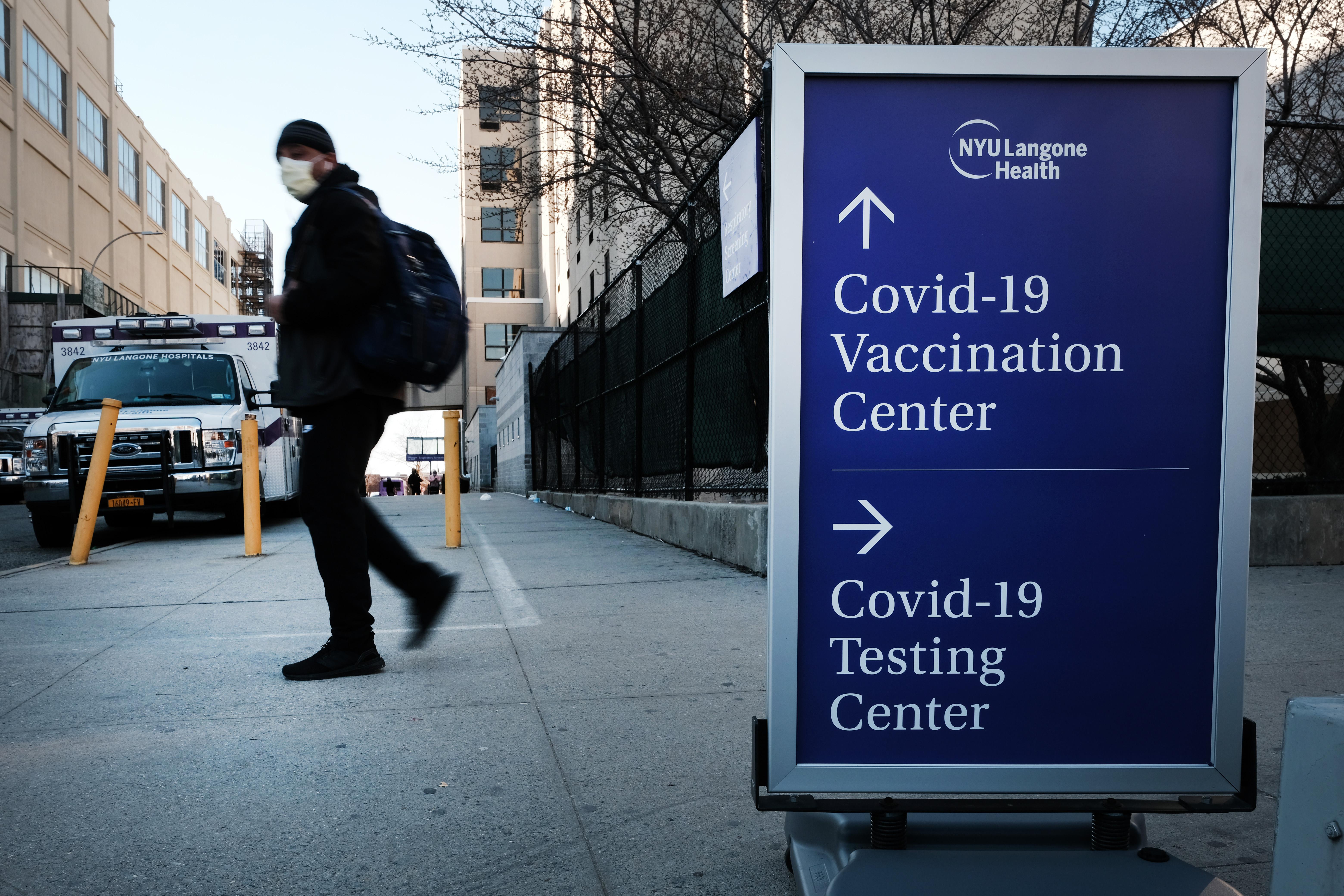 La gente camina junto a un letrero de una clínica de pruebas de Covid-19 y un lugar de vacunación de Covid fuera de un hospital de Brooklyn el 29 de marzo de 2021 en el distrito de Brooklyn de la ciudad de Nueva York.