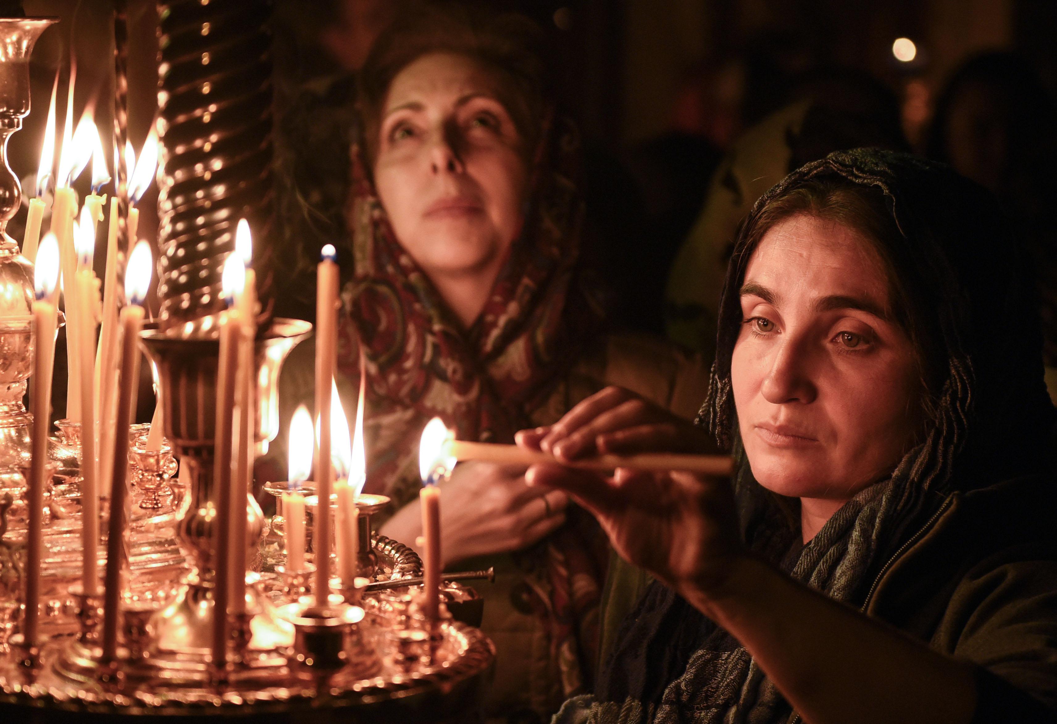 Mujeres encienden velas durante un servicio de Pascua en una iglesia en Bakú, a principios del 8 de abril de 2018.