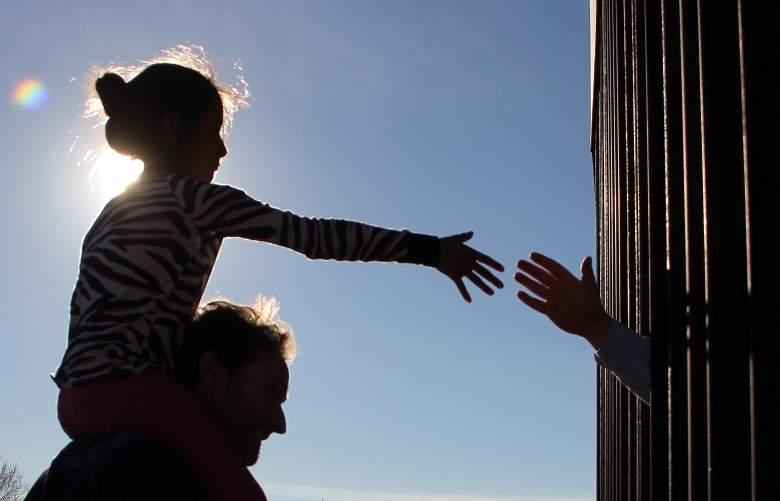 Una niña de Anapra, un barrio en las afueras de Ciudad Juárez en México, le da la mano a una persona en los Estados Unidos a través del cerco fronterizo, durante una oración con sacerdotes y obispos de ambos países para preguntar por los migrantes y la gente de la zona. , el 26 de febrero de 2019.