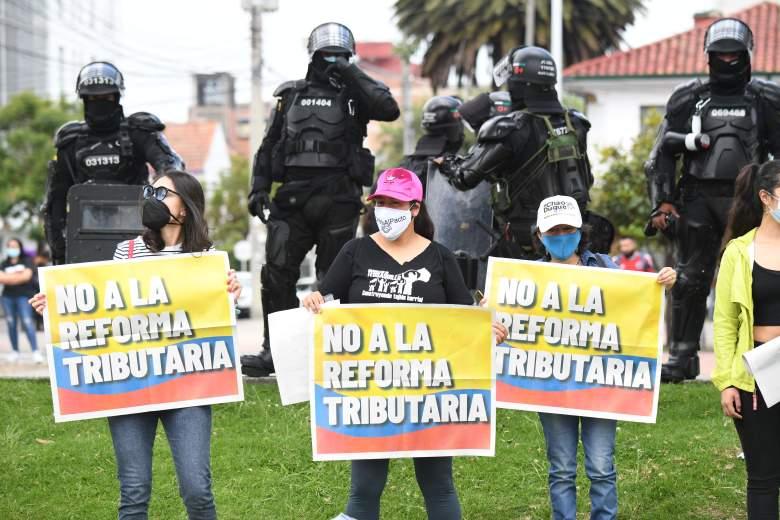 """Mujeres sostienen carteles con la bandera colombiana que dicen """"No a la reforma tributaria"""" durante una manifestación contra la reforma tributaria propuesta por el presidente colombiano Iván Duque, en Bogotá, el 28 de abril de 2021."""
