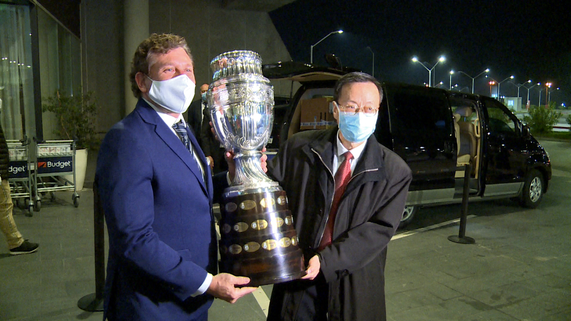 Screen grab showing Conmebol president, Paraguayan Alejandro Dominguez (L), and Chinese Ambassador in Uruguay Wang Gang, holding the Copa America trophy upon the arrival of 50,000 doses of the Chinese Sinovac vaccine against COVID-19 at the Carrasco International Airport in Ciudad de la Costa, Uruguay, on April 28, 2021. - The vaccines were donated by Chinese laboratory Sinovac to immunize South American football players, who will take part in the Conmebol Copa America and other tournaments. (Photo by Nicolas GARCIA / AFPTV / AFP) (Photo by NICOLAS GARCIA/AFPTV/AFP via Getty Images)