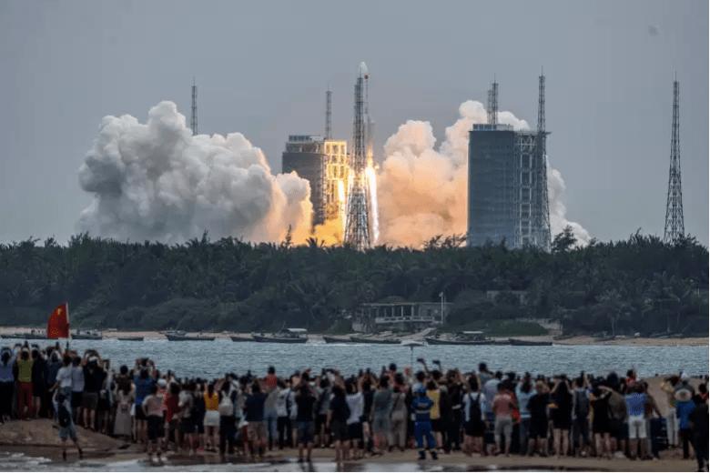 La gente observa un cohete Long March 5B, que transporta el módulo central de la estación espacial Tianhe de China, mientras despega del Centro de Lanzamiento Espacial Wenchang en la provincia de Hainan, en el sur de China, el 29 de abril de 2021.
