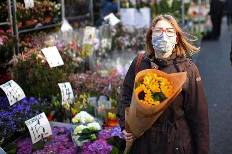 Una mujer que lleva una mascarilla protectora lleva un ramo de flores durante una visita al mercado de flores de Columbia Road en el este de Londres el Día de la Madre, 22 de marzo de 2020.
