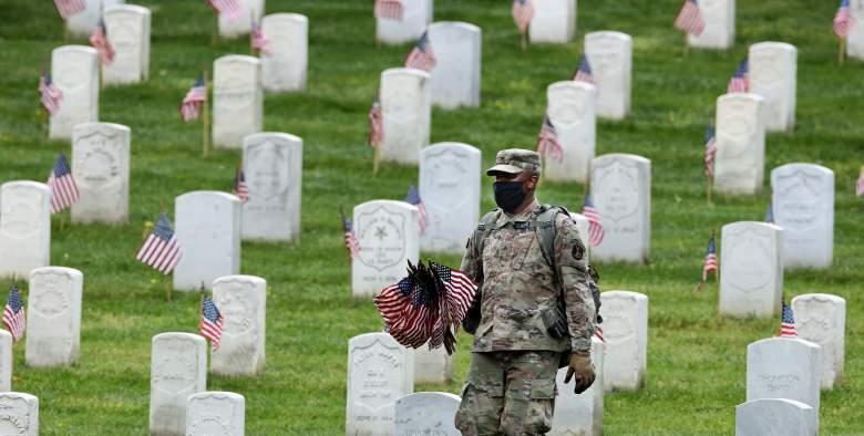 """Un soldado del 3er Regimiento de Infantería, o la """"Vieja Guardia"""", trabaja para colocar banderas de Estados Unidos frente a todas las tumbas delante del Memorial Día de fin de semana en el Cementerio Nacional de Arlington el 21 de mayo de 2020 en Arlington, Virginia."""