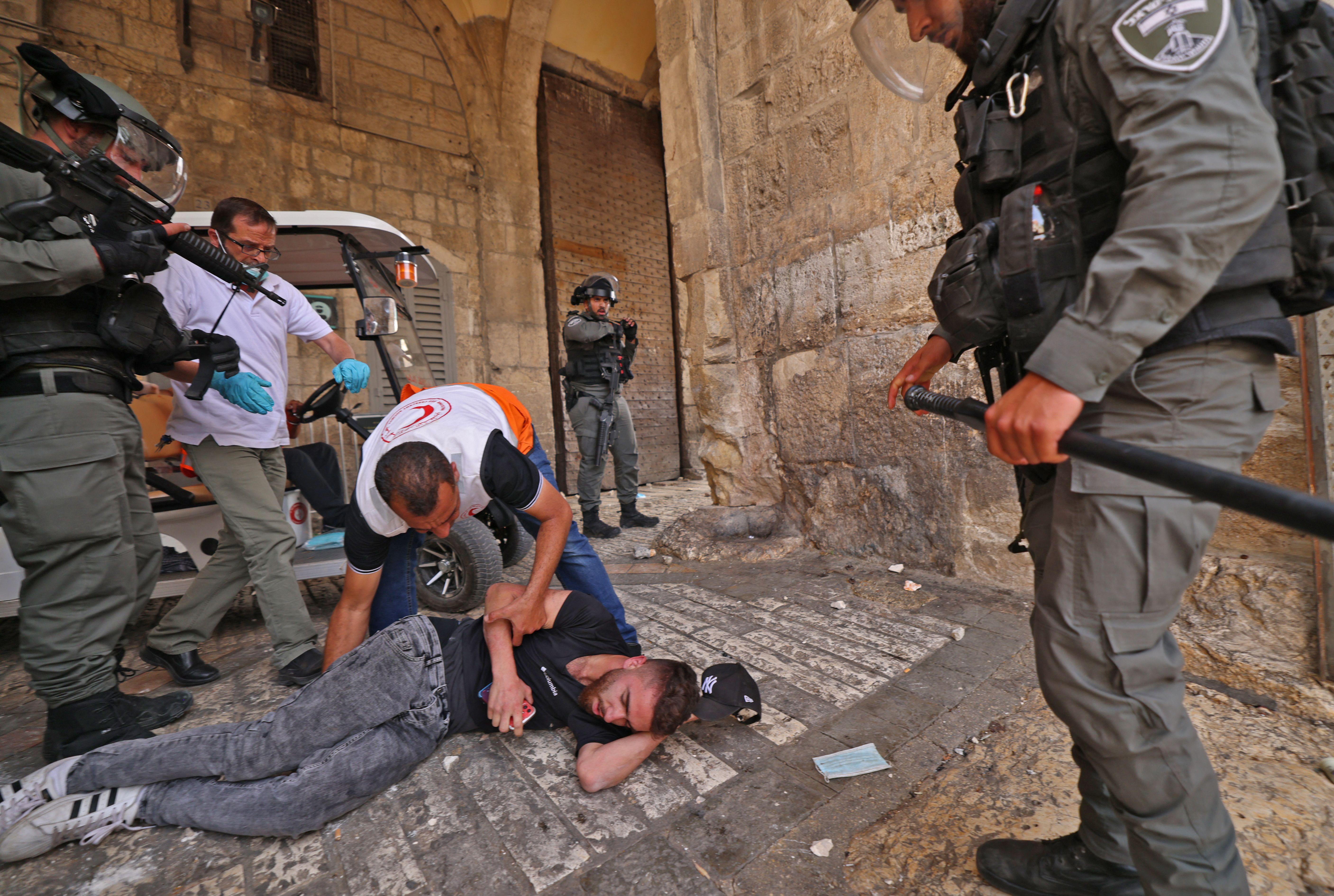 Los médicos palestinos ayudan a un manifestante herido en medio de enfrentamientos con las fuerzas de seguridad israelíes en la Ciudad Vieja de Jerusalén el 10 de mayo de 2021, antes de una marcha planificada para conmemorar la toma de posesión de Jerusalén por Israel en la Guerra de los Seis Días de 1967.