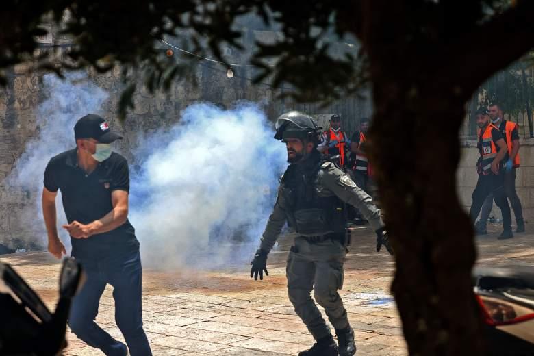 Los palestinos corren para refugiarse de los gases lacrimógenos lanzados por las fuerzas de seguridad israelíes en la Ciudad Vieja de Jerusalén el 10 de mayo de 2021.