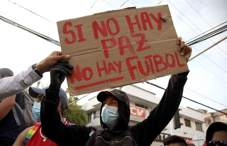 Un manifestante sostiene una pancarta que dice 'No hay paz, no hay fútbol' afuera del estadio Romelio Martínez en Barranquilla, Colombia, antes del inicio del partido de la Copa Libertadores entre América de Cali y Atlético Mineiro el 13 de mayo de 2021.