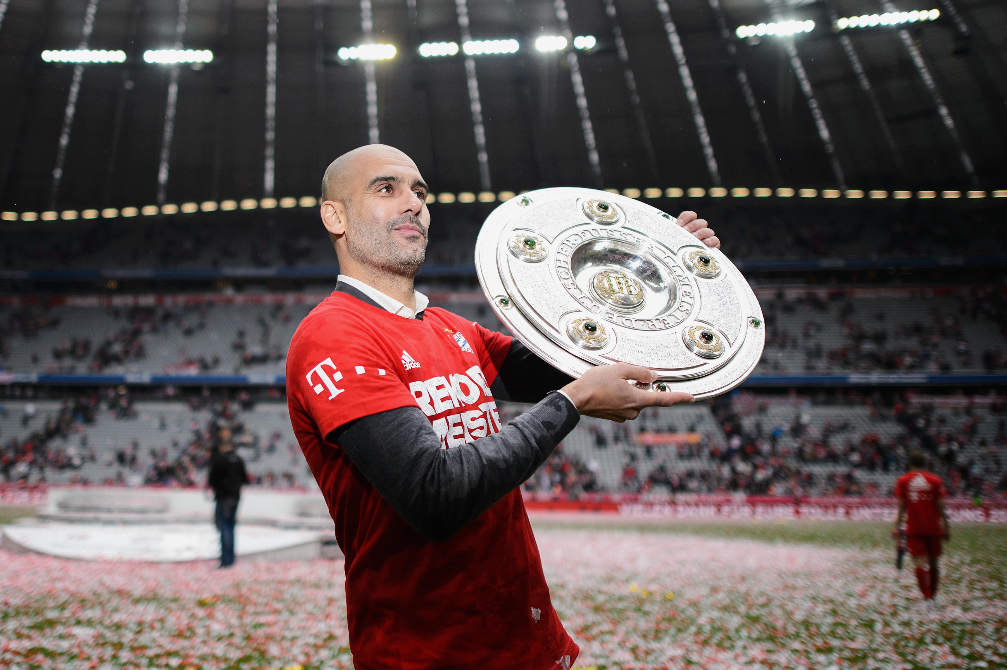 el entrenador Pep Guardiola de Muenchen celebra con el trofeo de la Bundesliga después de ganar la liga durante el partido de la Bundesliga entre el FC Bayern München y el 1. FSV Mainz 05 en el Allianz Arena el 23 de mayo de 2015 en Munich, Alemania.
