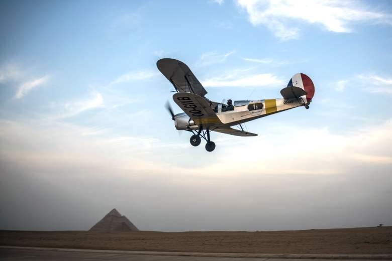 Los pilotos belgas Alexandra Maingard y su esposo Cedric Collette vuelan su biplano vintage Stampe OO-GWB cerca de las pirámides de Giza, en las afueras del sur de la capital egipcia, El Cairo, el 13 de noviembre de 2016 durante el Vintage Air Rally (VAR).
