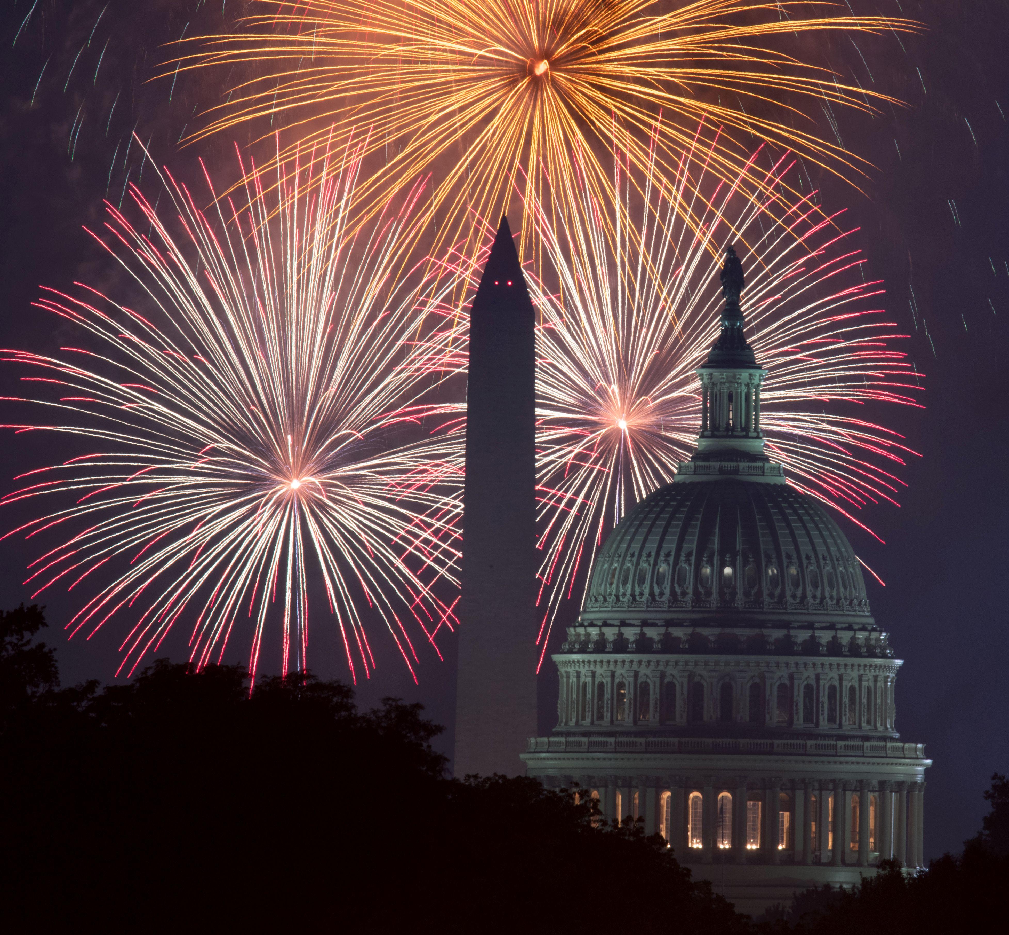Des feux d'artifice explosent au-dessus du National Mall à Washington, DC, alors que le Capitole des États-Unis (R) et le Monument national (C) sont vus le 4 juillet 2017 à Washington, DC.