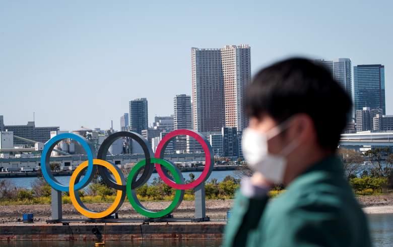 Un hombre con una mascarilla, en medio de las preocupaciones por la propagación del nuevo coronavirus COVID-19, se encuentra frente a los anillos olímpicos desde un punto de observación en el distrito de Odaiba de Tokio el 25 de marzo de 2020, el día después de la histórica decisión de posponer el Tokio 2020.