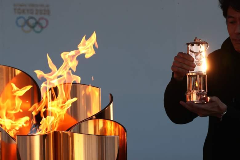 Un miembro del personal preserva la llama olímpica a la linterna durante la exhibición especial 'Llama de la recuperación' en el Parque Aquamarine un día después del aplazamiento de los Juegos Olímpicos y Paralímpicos de Tokio 2020