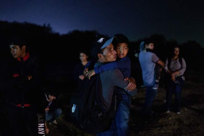 El hondureño Eric Villanueva, de 31 años, sostiene a su hijo Eric, de 7, mientras espera que lo lleven a un área de procesamiento de la Patrulla Fronteriza de los Estados Unidos después de cruzar la frontera entre Estados Unidos y México en una balsa hacia los Estados Unidos en Roma, Texas, a última hora del 9 de julio de 2021.