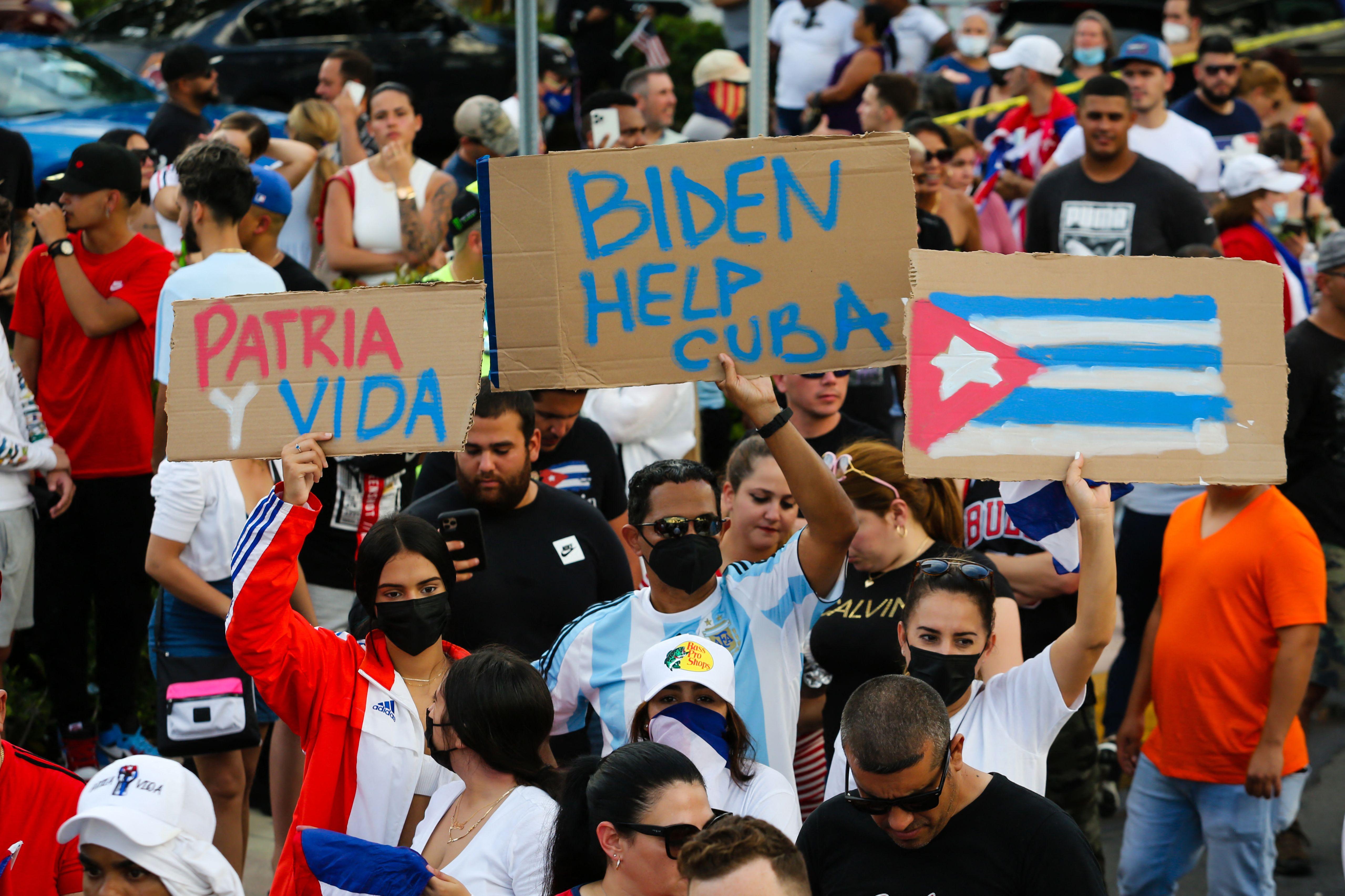 """La gente se manifiesta, algunos con pancartas que dicen """"Patria y Vida"""" y con la bandera nacional cubana, durante una protesta contra el gobierno cubano en Miami el 11 de julio de 2021."""