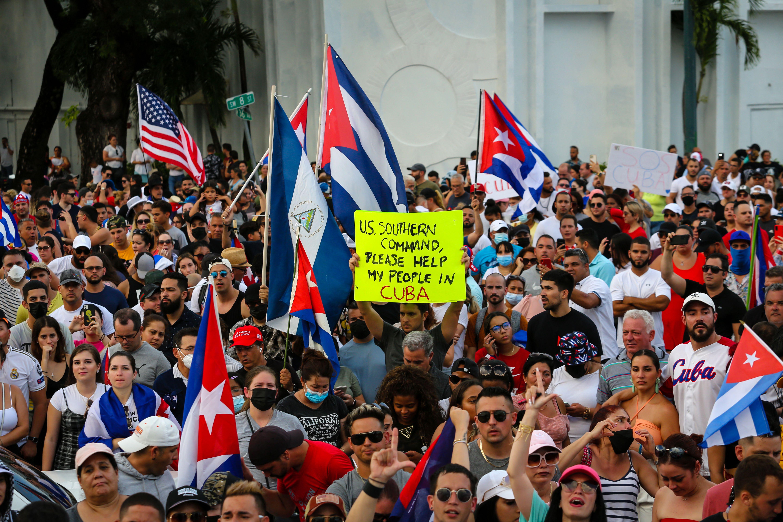 La gente se manifiesta, algunos con banderas y pancartas cubanos y nacionales de los Estados Unidos, durante una protesta contra el gobierno cubano en Miami el 11 de julio de 2021.