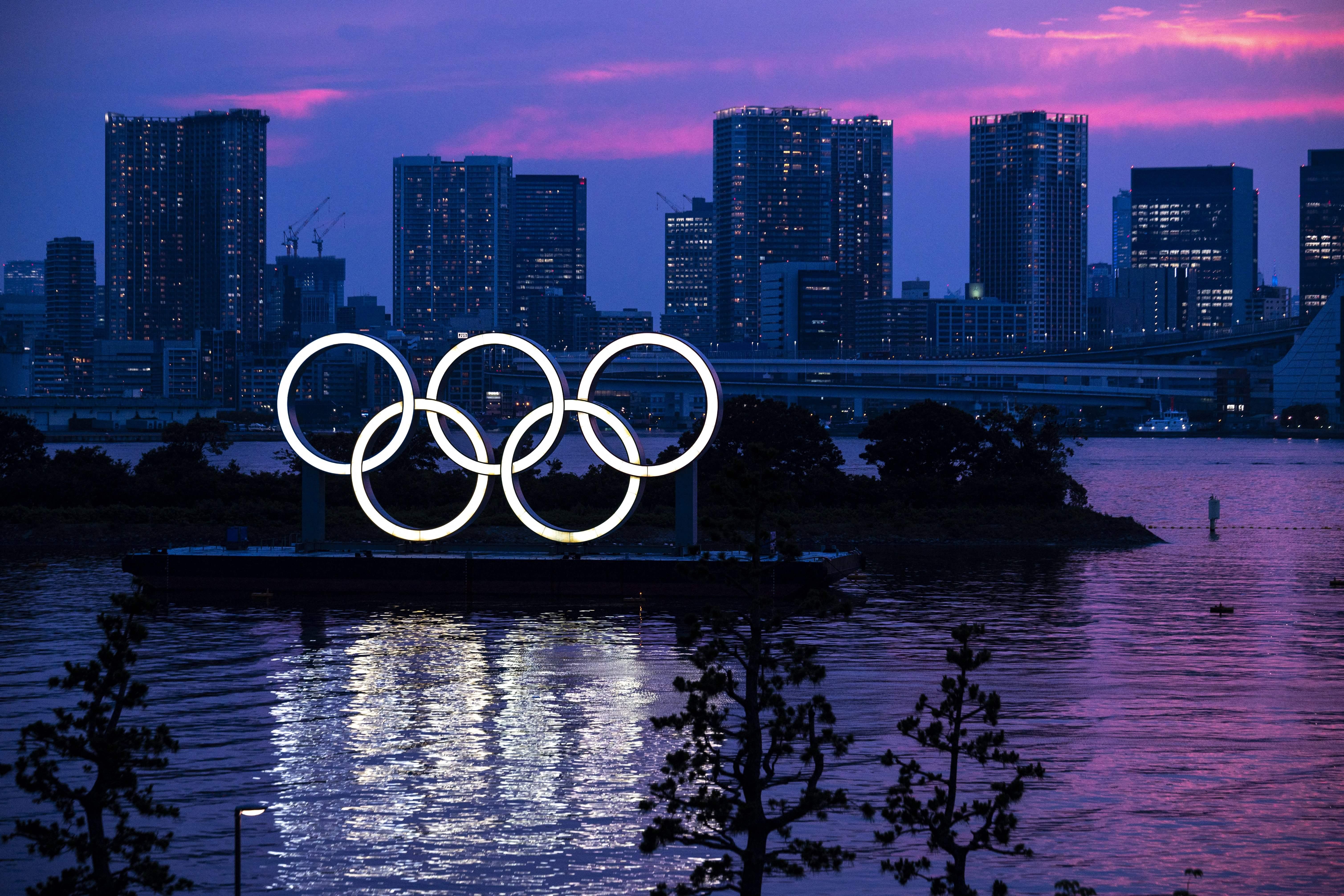 Una vista general muestra los anillos olímpicos iluminados al anochecer en el paseo marítimo de Odaiba en Tokio el 12 de Juky de 2021.