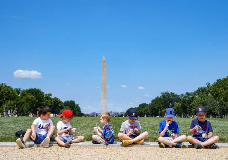 """Un grupo de niños se sienta a disfrutar de un helado del camión de helados """"America is Back"""" en el National Mall el 4 de julio de 2021 en Washington, DC."""