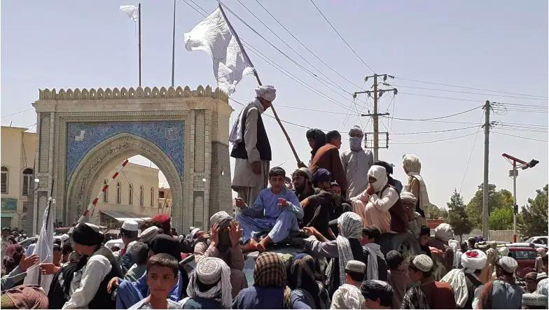 Los combatientes talibanes se paran en un vehículo a lo largo de la carretera en Kandahar el 13 de agosto de 2021.
