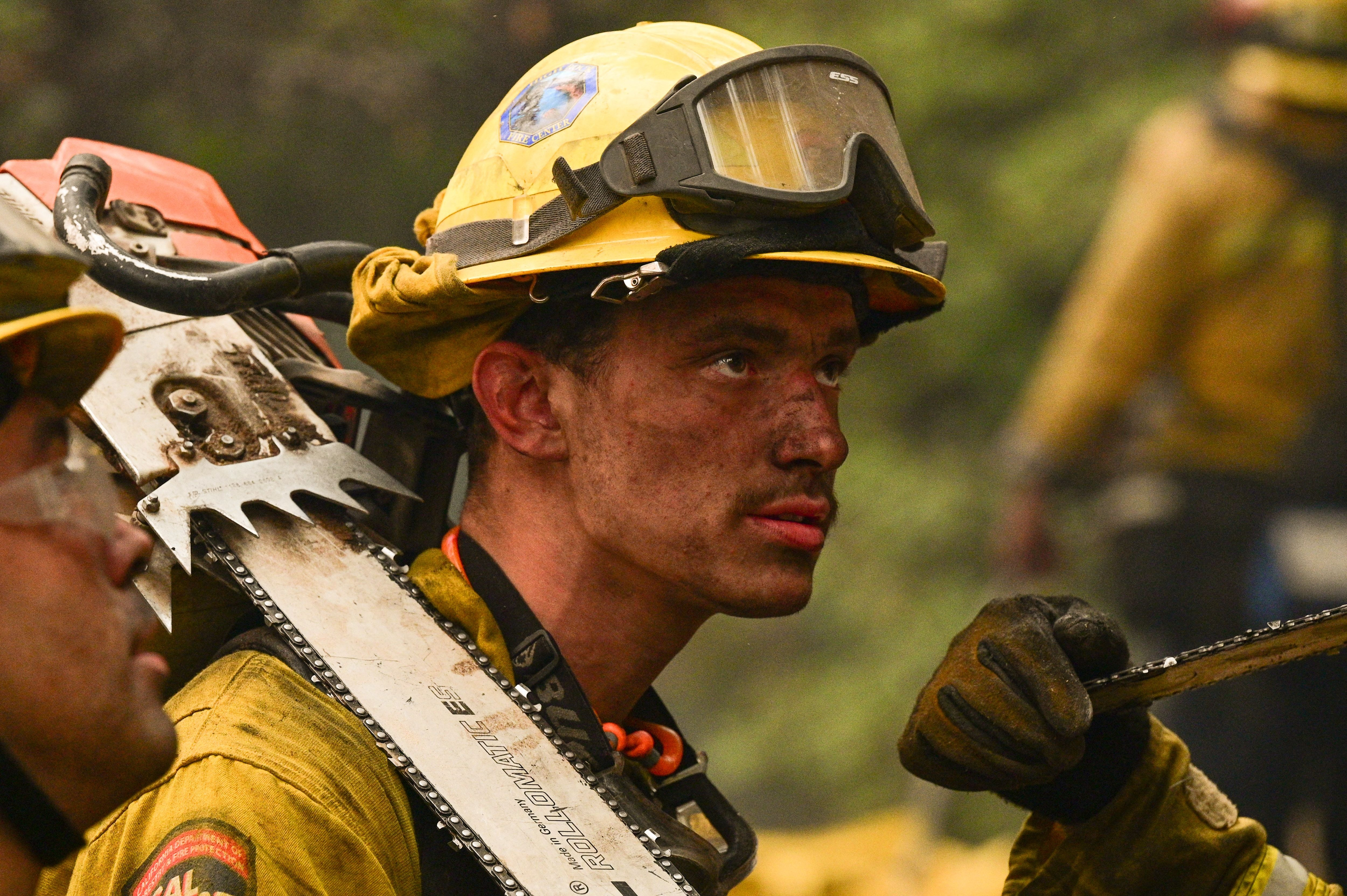On July 26, 2021, firefighters extinguished hot spots near the oldest mountain cabins on a hill in Dixie Fire, Twain, California.