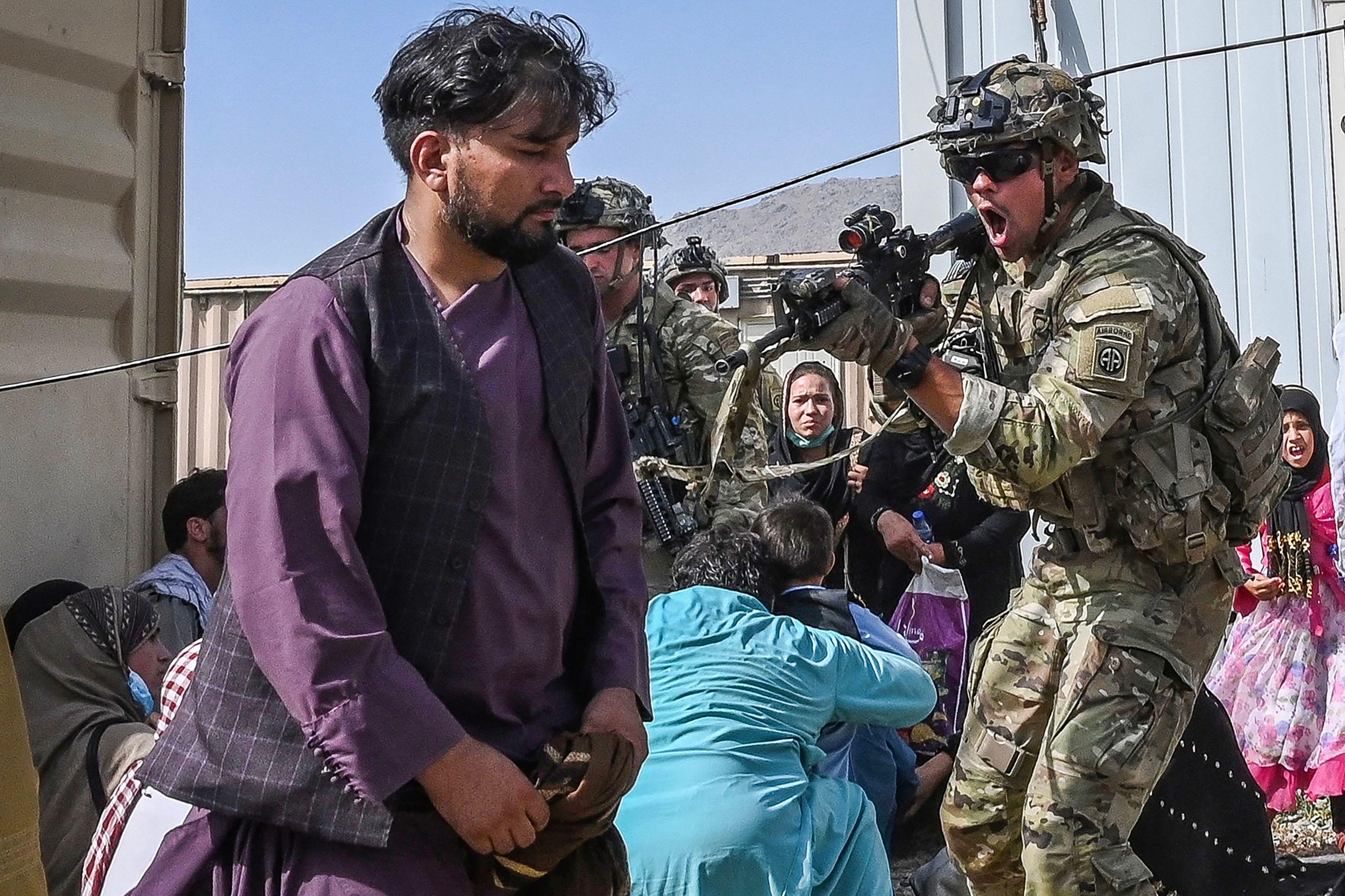 Un soldado estadounidense (C) apuntó su arma hacia un pasajero afgano en el aeropuerto de Kabul en Kabul el 16 de agosto de 2021, después de un final asombrosamente rápido de la guerra de 20 años de Afganistán, mientras miles de personas asaltaban el aeropuerto de la ciudad tratando de huir del grupo.