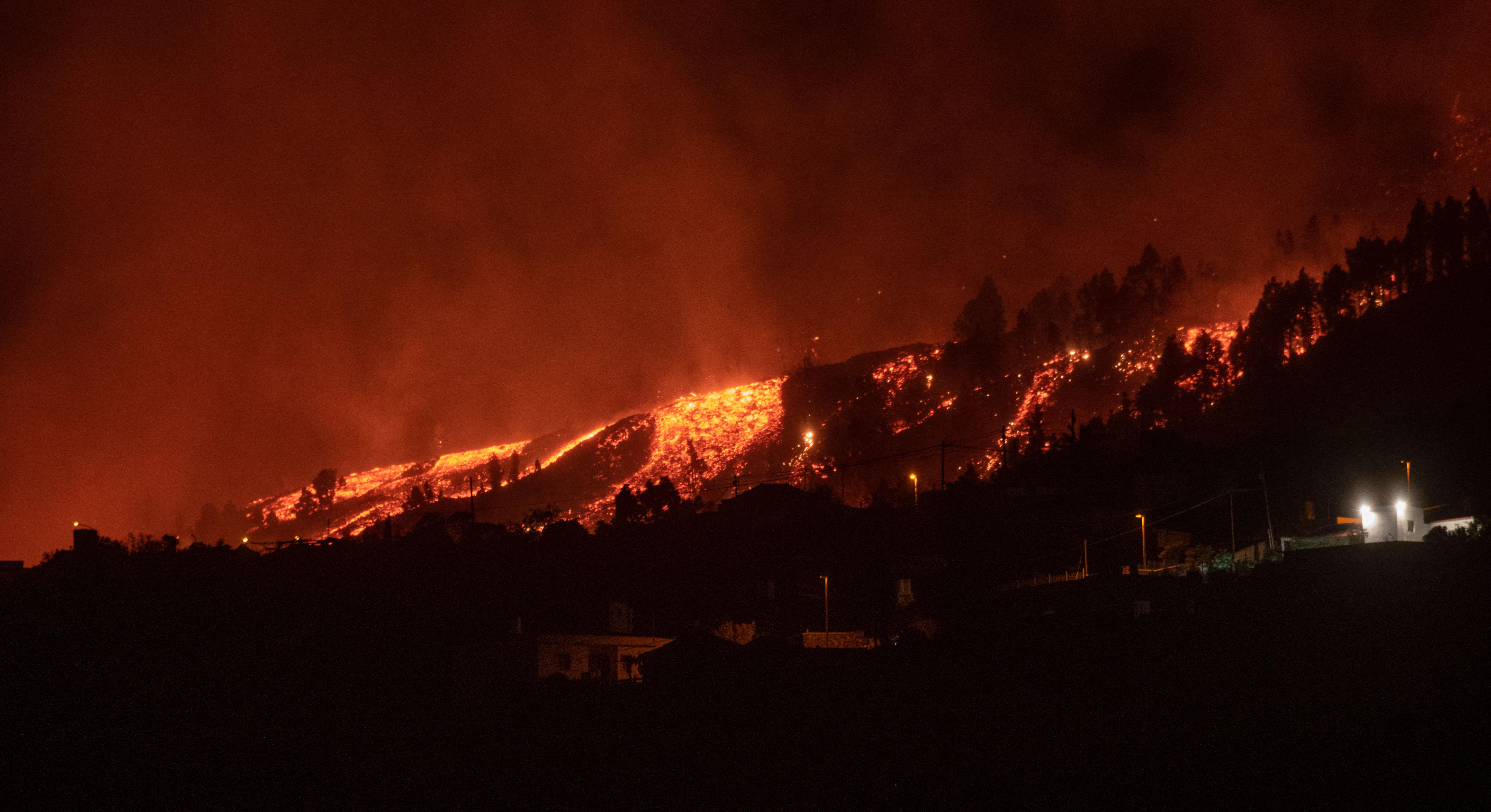 Los flujos de lava se acercan a las casas cuando el Monte Cumbre Vieja entra en erupción en El Paso, arrojando columnas de humo, ceniza y lava como se ve desde Los Llanos de Aridane en la isla canaria de La Palma, el 19 de septiembre de 2021.