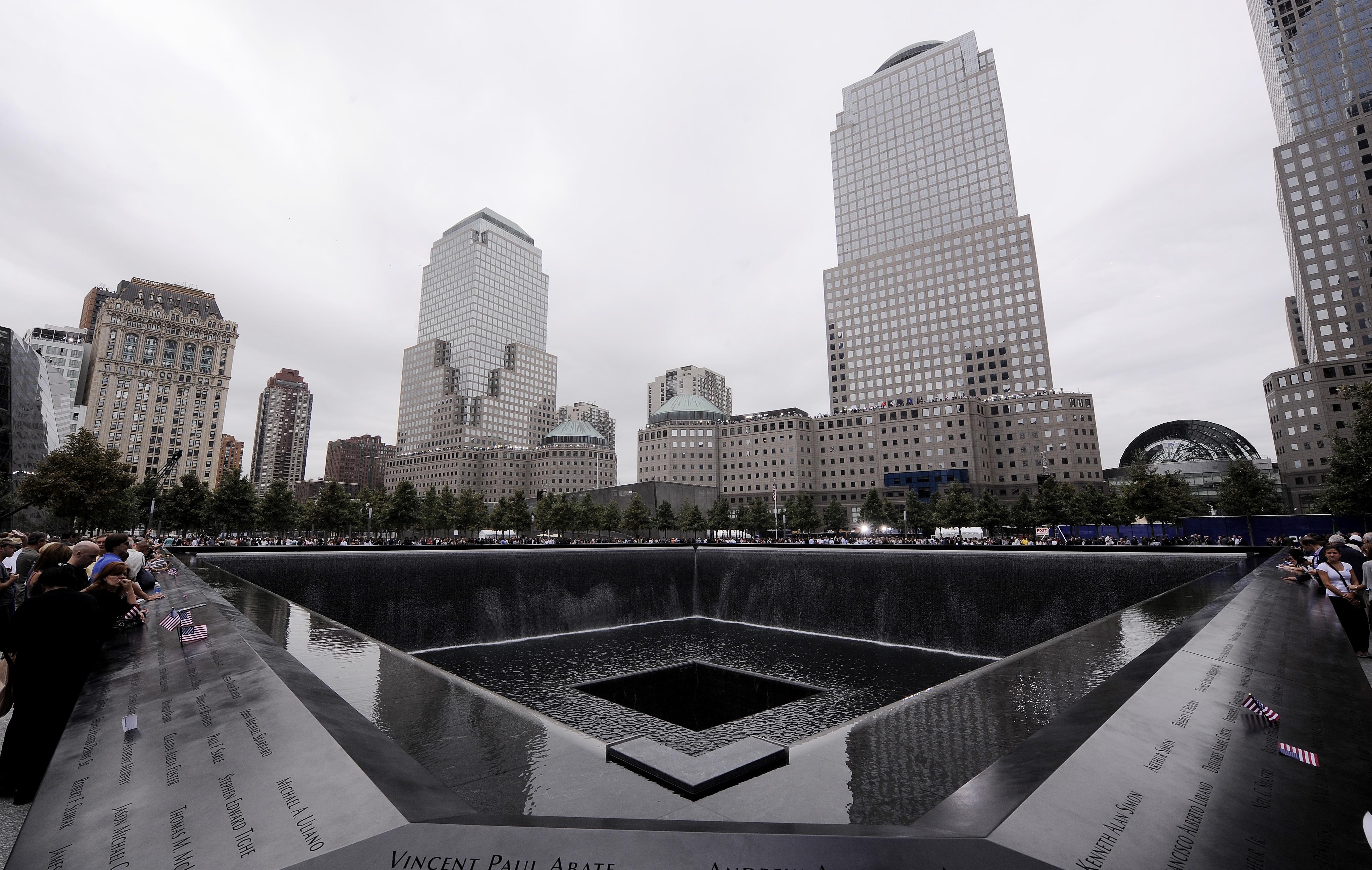 Los miembros de la familia se reúnen en el borde de la piscina norte del 9/11 Memorial durante las ceremonias del décimo aniversario de los ataques terroristas del 11 de septiembre de 2001 en el sitio del World Trade Center, 11 de septiembre de 2011 en Nueva Ciudad de York.