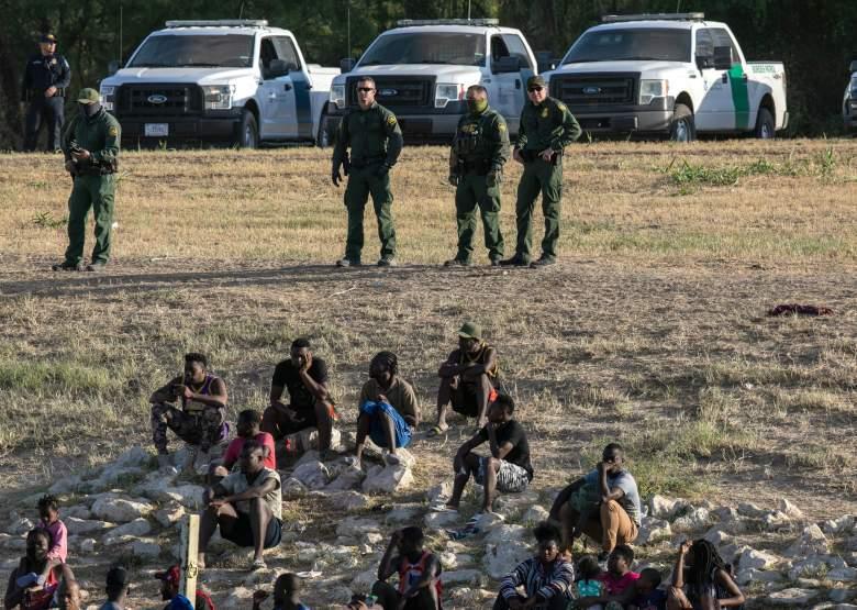 Agentes de la Patrulla Fronteriza de los Estados Unidos vigilan a los inmigrantes cerca de un campamento de migrantes en Del Rio, Texas, el 22 de septiembre de 2021, visto desde Ciudad Acuna, México.
