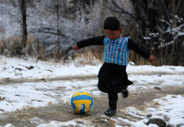 En esta fotografía tomada el 29 de enero de 2016, el niño afgano y fanático de Lionel Messi, Murtaza Ahmadi, de 5 años, usa una camiseta de bolsa de plástico mientras juega al fútbol en el distrito de Jaghori de la provincia de Ghazni.