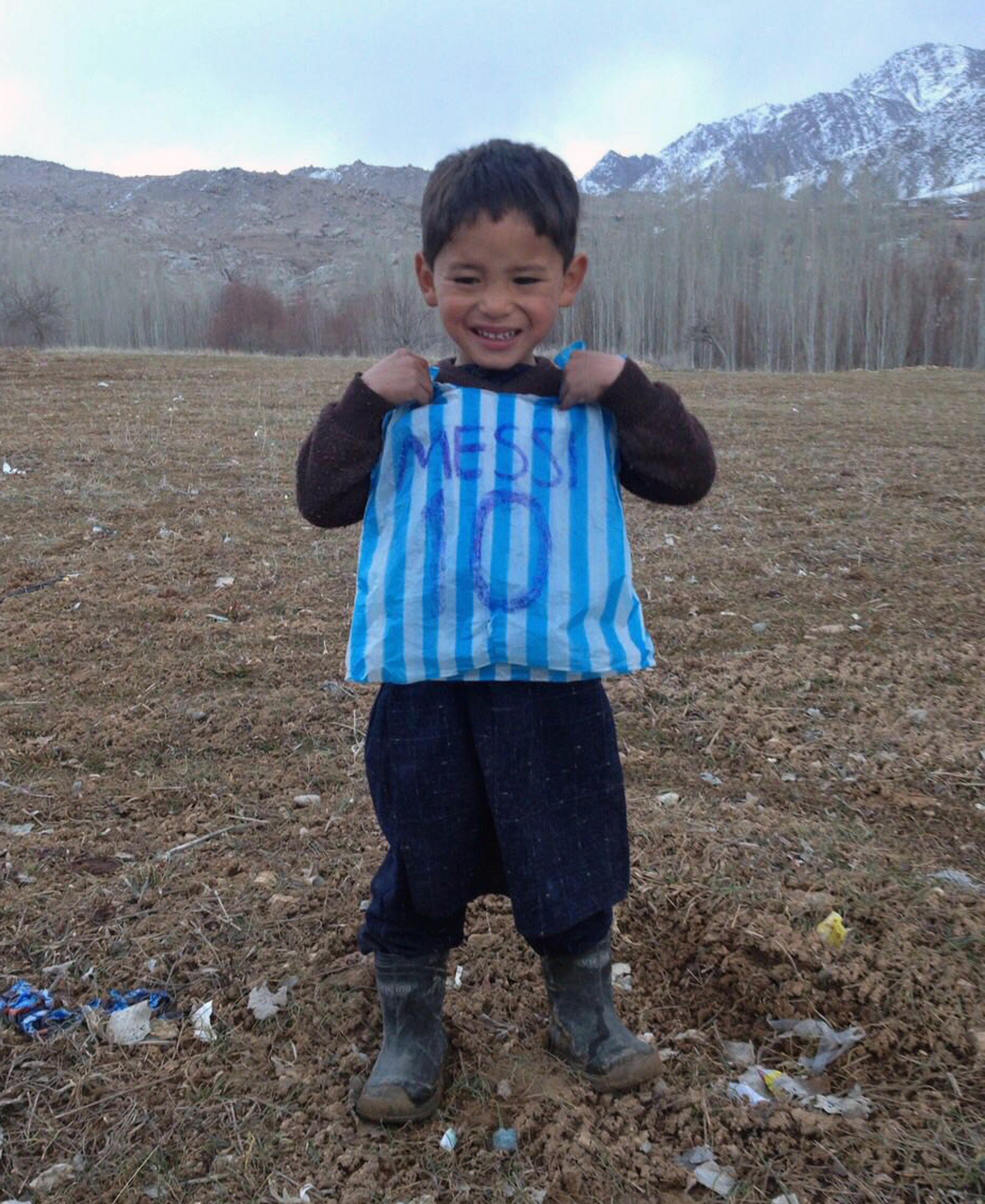 Esta fotografía tomada el 24 de enero de 2016 y proporcionada por la familia del niño afgano y fanático de Lionel Messi Murtaza Ahmadi, de 5 años, con su camiseta de bolsa de plástico en el distrito de Jaghori de la provincia de Ghazni.